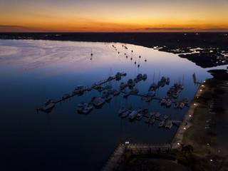 Aerial view of marina and sailboats at twilight.