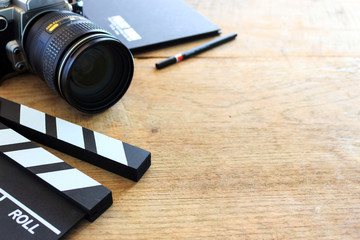 film director's desk. clapboard, book and digital camera on wood table with soft-focus and over light in the background