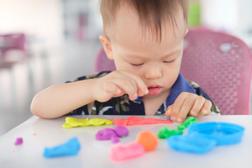 Cute little Asian 18 months old toddler baby boy child having fun playing colorful modeling clay / play dought at play school / child care, Educational toys for kid Creative play for toddlers concept