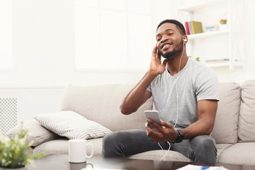 Young african-american man in earphones with smartphone
