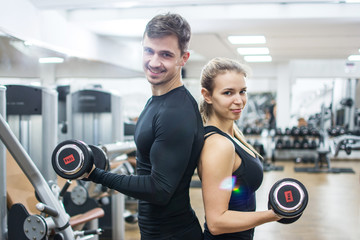 Couple lifting weights in gym.