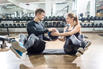 Sporty couple doing abdominal exercise with fitness balls at gym.