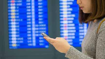 Woman traveller searching flight with information board at airport terminal