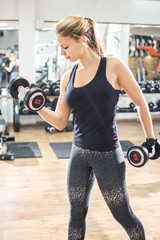 Fit blonde woman lifting weighs in gym.