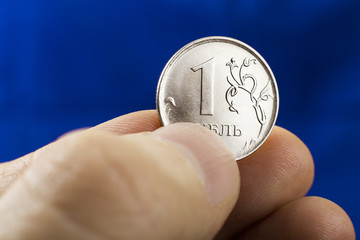 Close up of one ruble coin in the man's fingers on the dark blue background