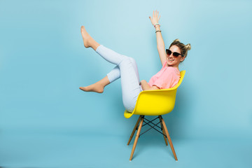 Fashionable young woman wearing sunglasses and casual clothes sitting on chair with raised legs and pointing up her hand, against a blue pastel background