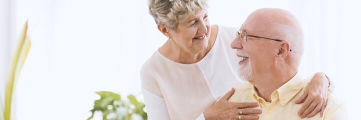 Happy grandmother hugging smiling husband