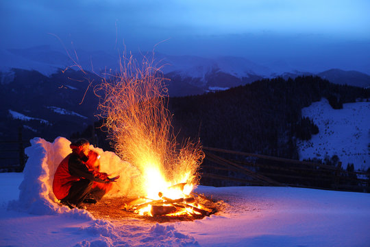 Two tourists are warming up at the fire