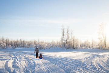 Mother and child sledding in winter