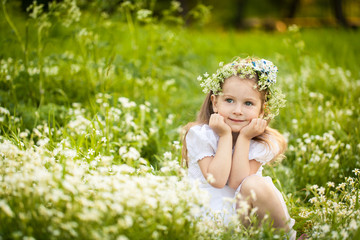 Little girl in a field with white flowers