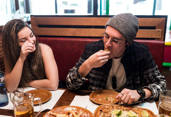 Young friends eating food in restaurant