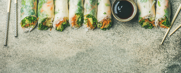 Helathy Asian cuisine. Flat-lay of vegan spring, summer rice paper rolls with vegetables, sauce, chopsticks over concrete background, top view, copy space, wide composition. Clean eating, dieting food