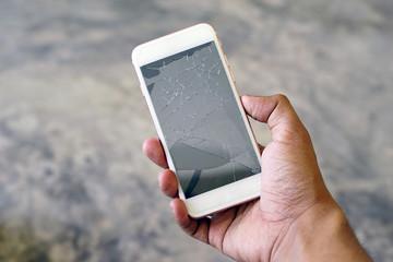 Businessman holding a crack smartphone. Shallow DOF.