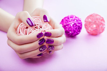 Woman with purple manicure holds a ball