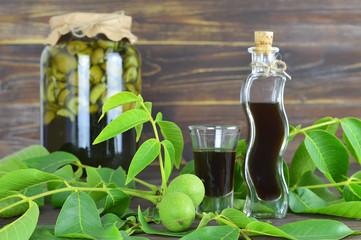 Green walnut liqueur on wooden background