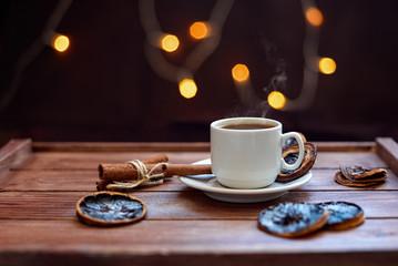 Чашка кофе с сушеными дольками лимона и палочками корицы на деревянном коричневом фоне с огнями гирлянды