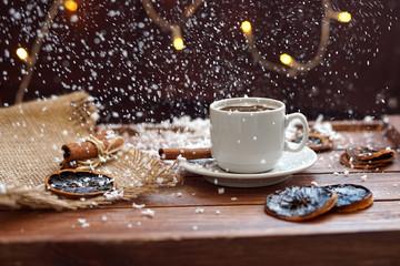 Чашка кофе с салфеткой из мешковины, сушеными дольками лимона и палочками корицы на деревянном коричневом фоне с огнями гирлянды под падающим снегом