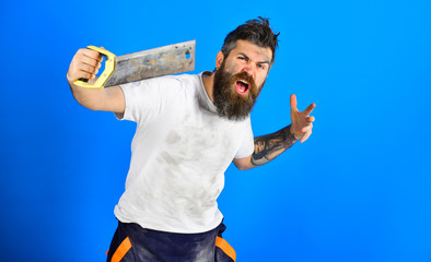 Angry carpenter concept. Guy with beard covered with dust.