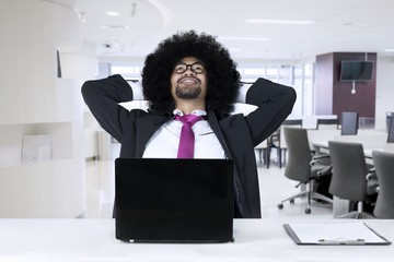 African american with laptop relaxing at office