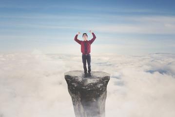 Asian businessman celebrating his success on mountain