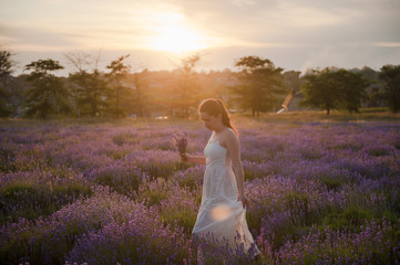 pretty young woman in dress with bouquet of flowers in lavender field at sunset in summer