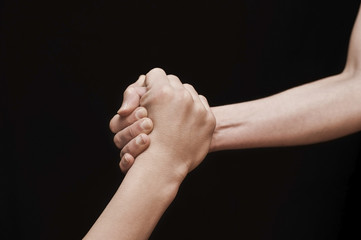 Concept of help on black background. One hand pulls another hand, helping her on a black background