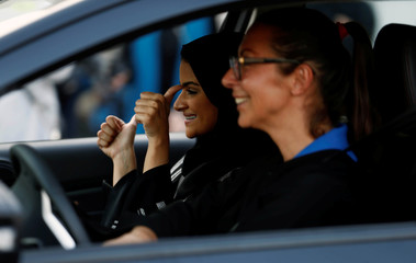 Saudi woman gestures as she sits in a car during a driving training at a university in Jeddah