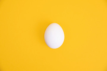 One white egg on yellow background.