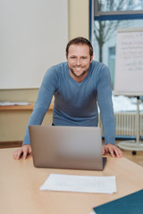 Smiling friendly businessman standing over a pc