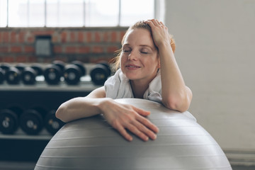 Young woman relaxing in a gym with a pilates ball