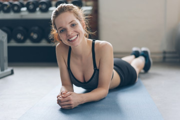 Happy athletic young woman relaxing on a mat