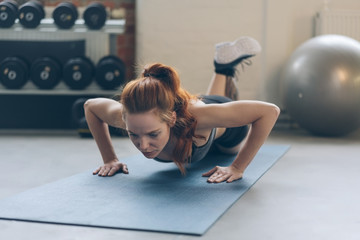 Fit young woman working out doing press ups