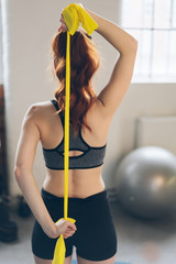 Young redhead woman suing exercise straps