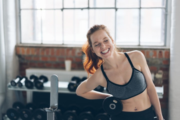 Laughing vivacious young woman in a gym