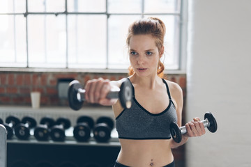 Fit young woman working out lifting weights