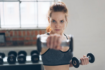 Focused determined young woman lifting weights