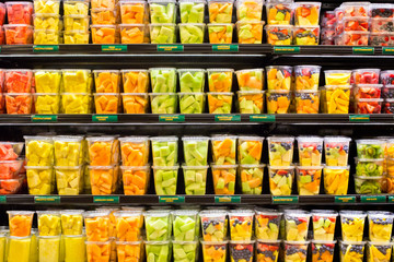 Assortment of fresh cut fruit in plastic containers  in supermarket grocery display case
