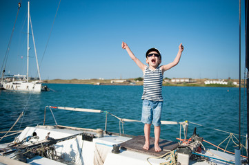 cute little boy in captain hat and sunglasses on yacht screams joyfully waving his hands
