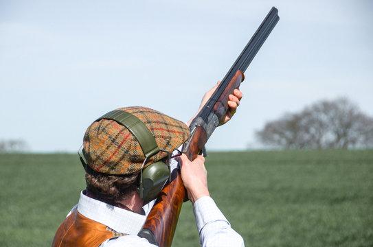 A man with shotgun clay pigeon shooting