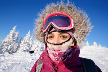 Girl is making a selfie in ski mask, in background there is snow. His hair was icy with frost, initsi action camera.