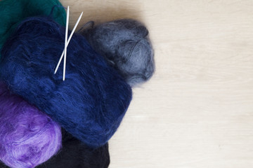 Colored balls of wool with knitting. With background space