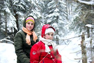 Two happy little girls in snowy forest