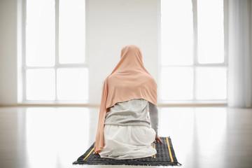 Young Muslim woman praying, indoors