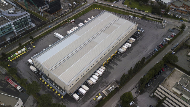 Aerial view of a large shed that is used as a warehouse for loading and unloading parcels. Many trucks are parked around the facility for their work. All within an industrial area.