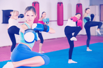 Portrait of girl who is boxing with group in gym