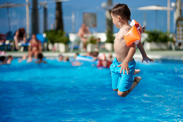 European child having fun jumping into the pool.