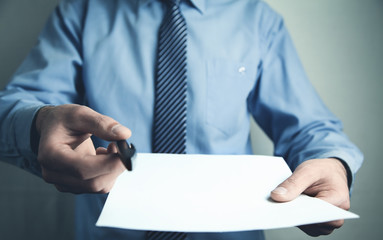 Man showing pen and blank paper.
