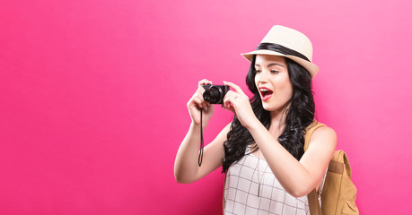 Traveling young woman holding a camera on a solid background
