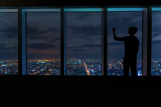 Man looking out large windows high above a sprawling city at night