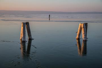 idyllischer Steg auf gefrorenem See bei Sonnenuntergang